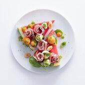 Watermelon pizza with cured ham, melon balls, mozzarella and parsley pesto