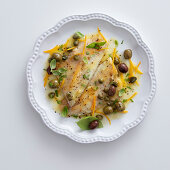 Sea bass fillets with citrus fruits, olives and capers