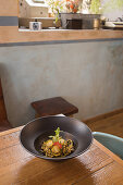Noodles with zucchini garnished with pesto sauce and cherry tomatoes placed on table in kitchen