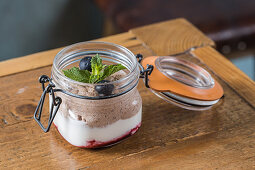 Chocolate mousse garnished with blueberries and sprig of mint and placed on wooden table in cafe