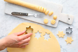 Biscuits being cut out of rolled out pastry