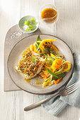 Fish fillet with a herb and orange crust and vegetables noodles