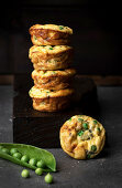 Still life of stacked pea muffins against dark background