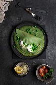 still life of pea crepes served on a dark dish placed on dark textured board