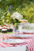 Flowers and place settings on summery garden table