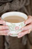 Cup of chai tea held in hands