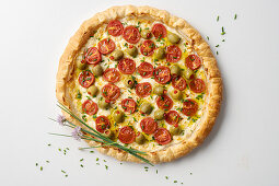 A puff-pastry pizza with cherry tomatoes and stuffed olives