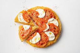 Spaghetti omelette pizza with tomatoes and mozzarella