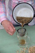 Straining tea from dried parts of plants into a glass