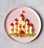 A fruit castle made with bananas, strawberries and apple