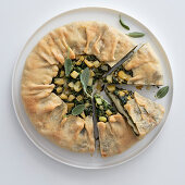 A round cheese and herb pie with apples and sage