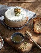 Baked camembert with walnuts on wooden table