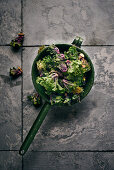 Flower sprouts (a cross between kale and Brussels sprouts) in a vintage sieve