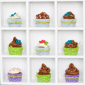 Cupcakes with colorful cupcake liners and sugar flowers in a box display