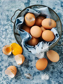 Brown eggs in bowl, some of them broken