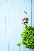 Grüner Blattsalat und Früchte auf hellblauer Holzfläche