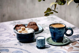 Cup of turkish black coffee with milk, sugar cubes and cookies