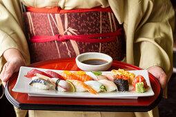 A woman wearing a kimono holding a tray of sushi