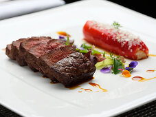 Roasted Beef steak with stuffed pepper, herbs and flowers