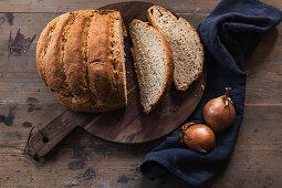 Onion bread baked in a pot on a rustic wooden board