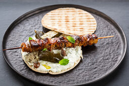 Greek pita bread filled with meat skewer and tzatziki