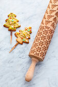 Rolling pin with Christmas motifs and Christmas tree biscuits on a stick