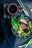 Asian noodle soup with grilled duck breast and pak choi