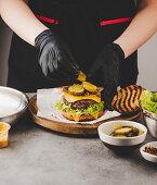 Arrange pickles on cheeseburgers
