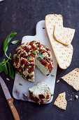 Cheese ball with dried tomatoes, pine nuts and pesto