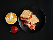 Hearty breakfast with ham on toast and cappuccino