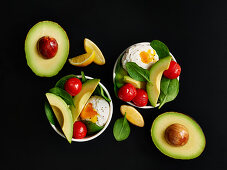 Small breakfast bowls with egg, avocado and braised tomatoes