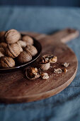 Walnuts in the shells and opened on a wooden board