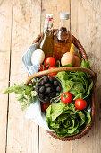 A basket of lettuce, tomatoes, eggs, olives, oil and vinegar