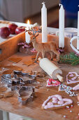 Wooden board with candles, deer figure, rolling pin, gingerbread, and cookie cutters
