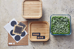 Frozen peas in glass storage containers with wooden lids