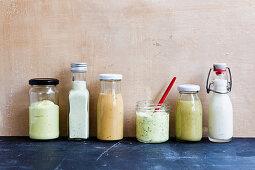 Various vegan salad dressings in glass vessels