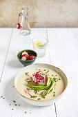 Creamy potato soup with green asparagus and radish