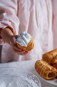 Little girl hand holding sweet pastry with cream