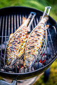 Grilled trout in fish grilling baskets on the barbecue