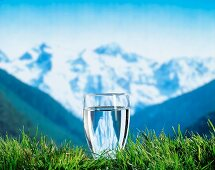 Glass of water with mountains in the background