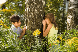 Girl and boy playing hide-and-seek, children's birthday party