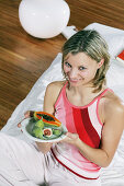 Young woman relaxing in bed with a plate of exotic fruits