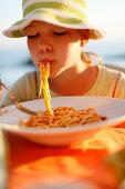 Girl eating spaghetti, Formentera, Balearic Islands, Spain