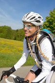 Young woman riding a racing bicycle, Upper Bavaria, Germany