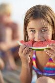Girl eating a slice of melon, lake Starnberg, Upper Bavaria, Bavaria, Germany