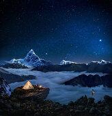 Night sky over snowcapped mountains, Man camping near prayer flags, Pokhara, Kaski, Macchapucchare, Annapurna, Nepal, Asia