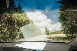Looking through the front window of the car with the map on the dash board, road in the country side, Halland, Sweden