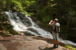 Mann fotografiert die Rissloch-Wasserfälle bei Bodenmais, Bayrischer Wald, Bayern, Deutschland
