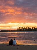 Paar bei Sonnenuntergang am Strand mit Palmen, Insel Boipeba, Bahia, Brasilien, Südamerika