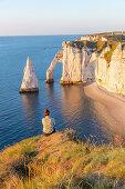 Eine Frau sitzt an der Alabasterküste und betrachtet den Felsbogen Porte d'Aval (Elefantenrüssel) und die Felsnadel Aiuille bei Étretat, Normandie, Frankreich